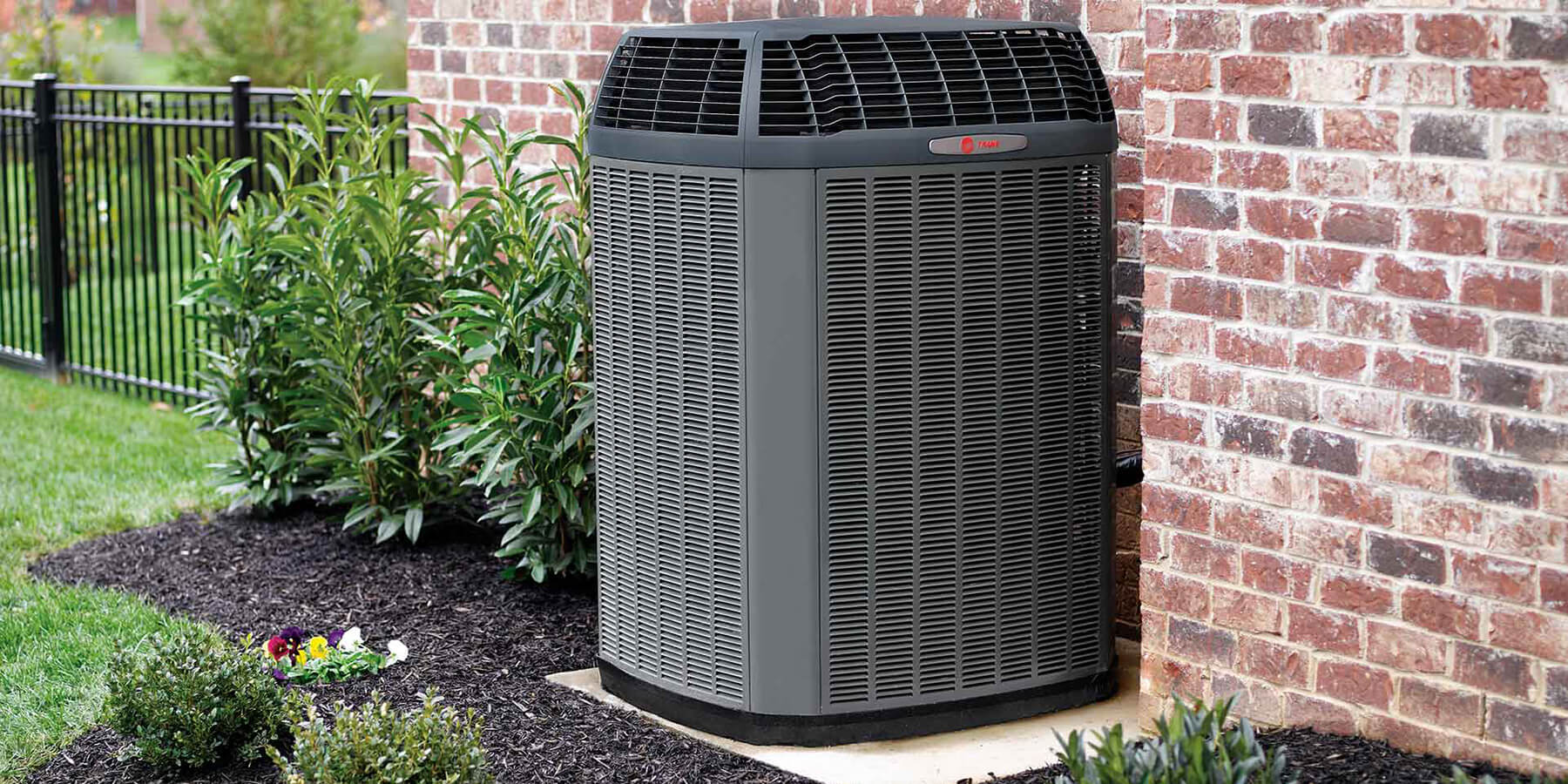 Trane air conditioning unit installed outside of brick home.